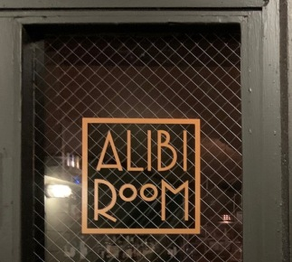 The Alibi Room door/sign, which is tucked into Post Alley. Photo by Cecilia Kennedy.